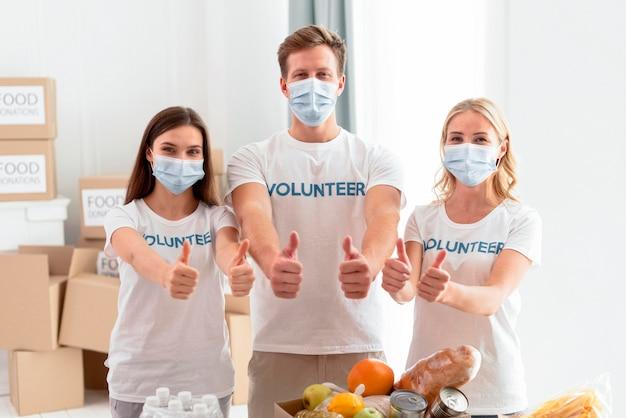 Вид спереди веселых добровольцев на день еды, поднимающих палец вверх Premium Фотографии