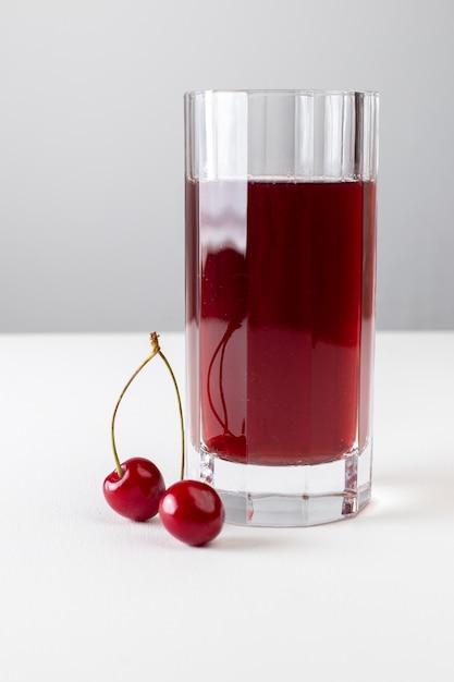 白い表面の長いガラスの中のチェリージュースの正面図 無料写真