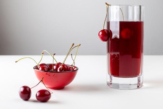 白い表面に新鮮なチェリーと長いガラスの中のチェリージュースの正面図 無料写真