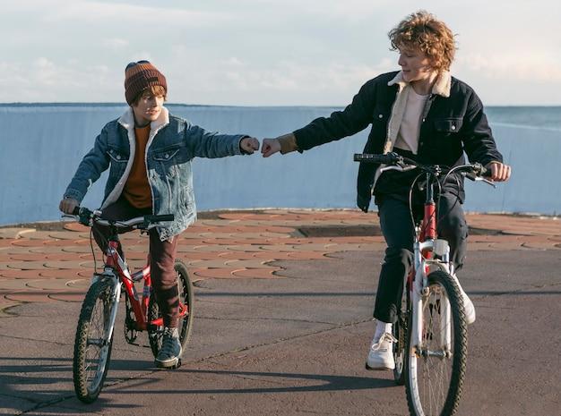 自転車に乗って屋外の子供友達の正面図 無料写真