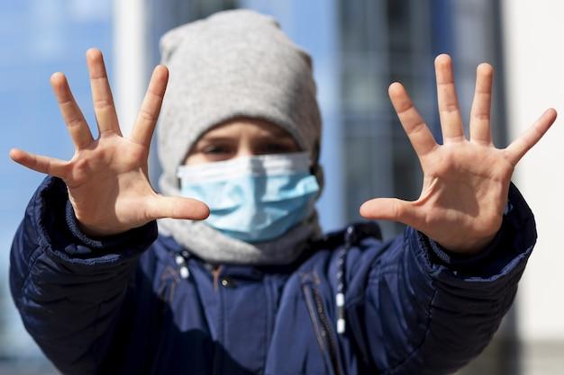 外の医療用マスクを着用しながら手を示す子供の正面図 無料写真
