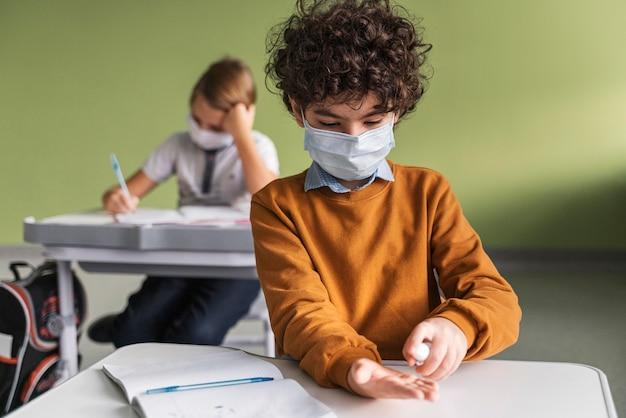 Вид спереди ребенка с медицинской маской, дезинфицирующей руки в классе Бесплатные Фотографии