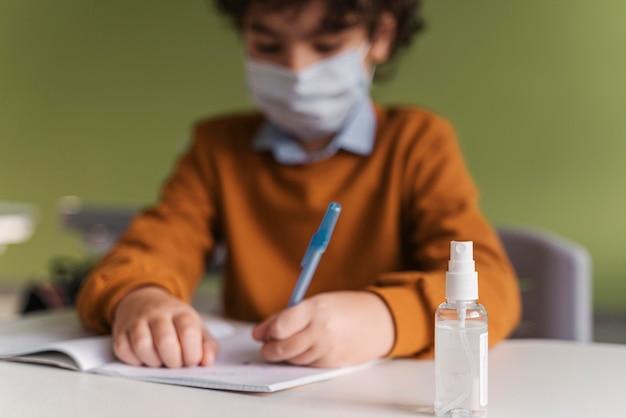 机の上に手指消毒剤のボトルとクラスの医療マスクを持つ子供の正面図 無料写真