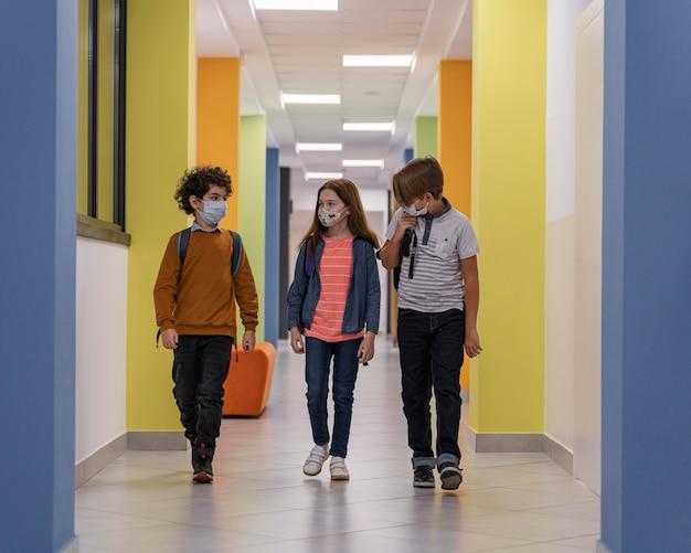 Вид спереди детей в школьном коридоре с медицинскими масками Бесплатные Фотографии