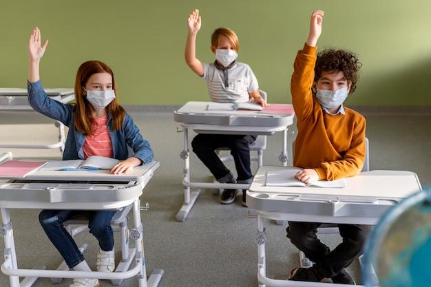 手を上げて学校で医療マスクを持つ子供たちの正面図 無料写真
