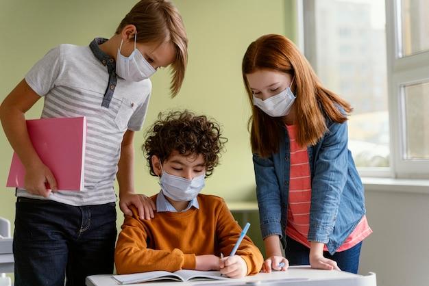 Вид спереди детей с медицинскими масками, обучающимися в школе Бесплатные Фотографии