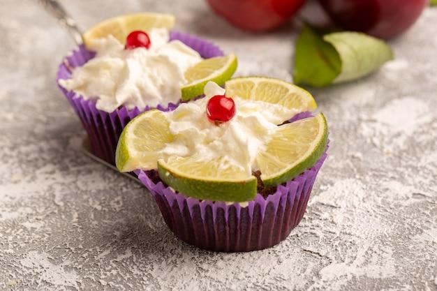 プラムと一緒にクリームとレモンのスライスとチョコレートブラウニーの正面図 無料写真