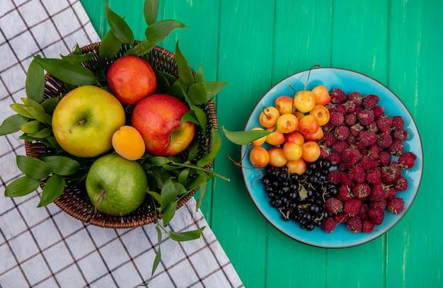 緑の表面のプレートに白いサクランボラズベリーと黒スグリのバスケットの着色されたリンゴの正面図 無料写真