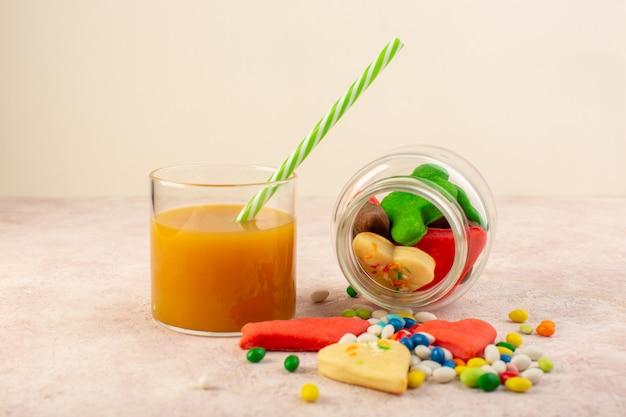 Вид спереди красочных вкусных печений различных форм внутри банка с конфетами и свежим персиковым соком Бесплатные Фотографии