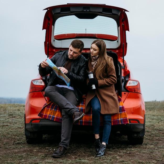 Вид спереди пары, проверяющей карту в багажнике автомобиля Бесплатные Фотографии