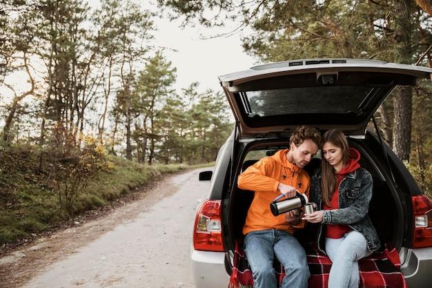 Вид спереди пара, наслаждающаяся горячим напитком во время поездки Бесплатные Фотографии