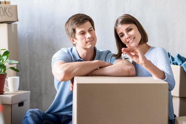 Вид спереди пары, держащей ключи от нового дома, собирая вещи для выезда Бесплатные Фотографии