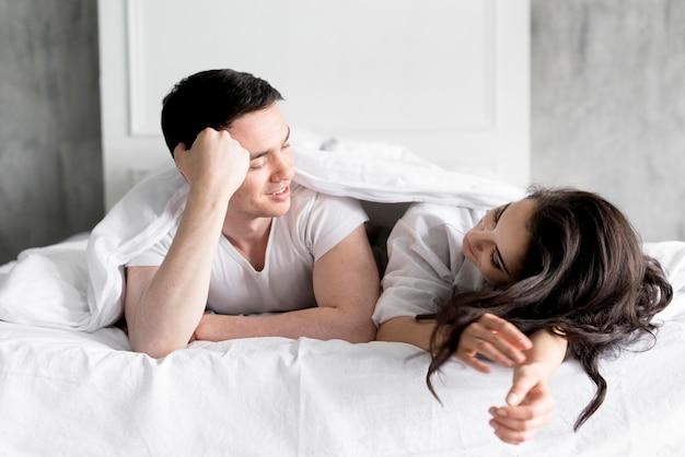 自宅のベッドでカップルの正面図 無料写真
