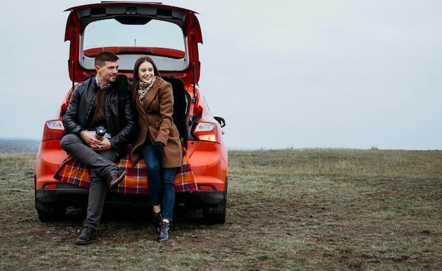 Вид спереди пары, сидящей в багажнике автомобиля с копией пространства Бесплатные Фотографии