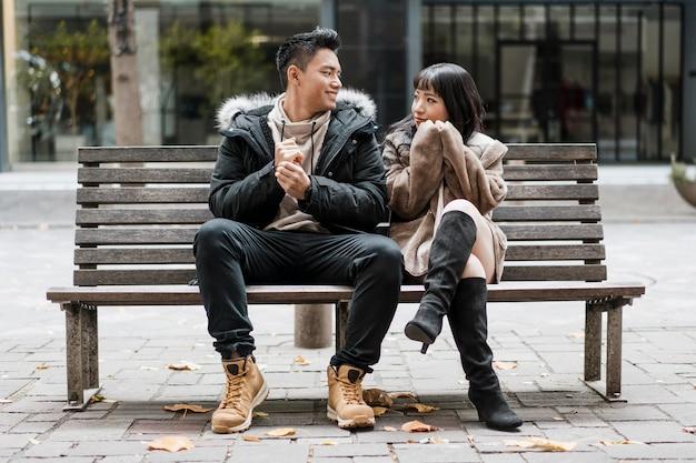 Вид спереди пара, сидящая на скамейке вместе Premium Фотографии