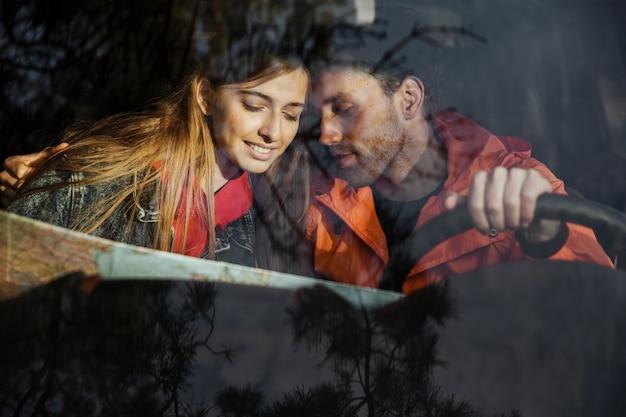 Вид спереди пара с картой в машине, отправляющейся в поездку вместе Бесплатные Фотографии