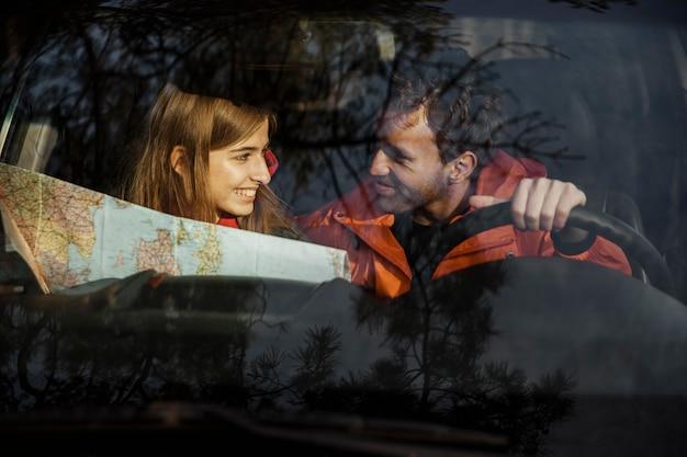 Вид спереди пара с картой в машине, собирающейся в поездку Бесплатные Фотографии