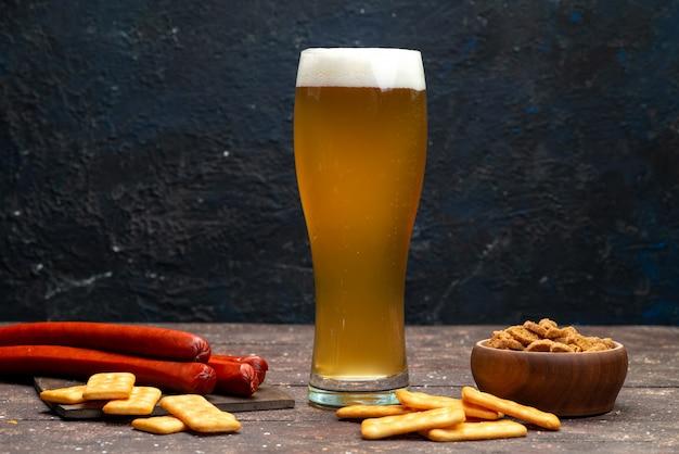 暗い表面にビールと共にクリスプとクラッカーの正面図 無料写真