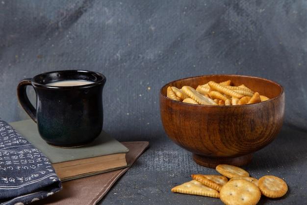 灰色の表面に塩味のクラッカーとミルクブラックカップのカップの正面図 無料写真
