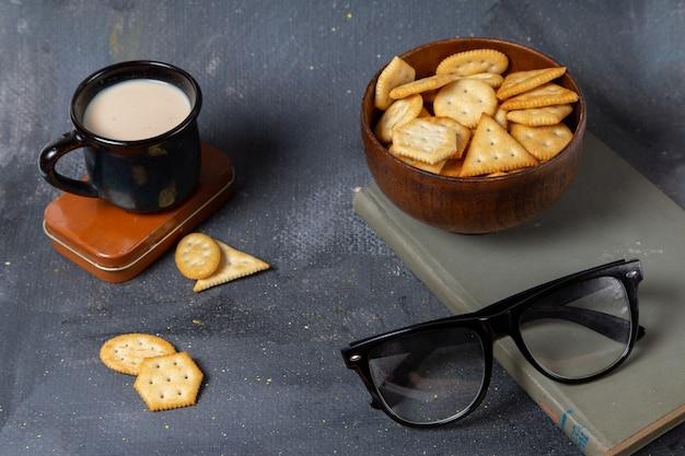 灰色の表面にクラッカーとサングラスと牛乳のカップの正面図 無料写真