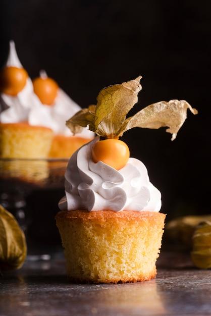 アイシングとフルーツのカップケーキの正面図 無料写真