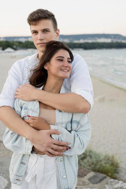 Вид спереди милая пара в объятиях на открытом воздухе Бесплатные Фотографии
