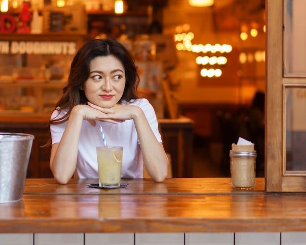レモネードを飲むかわいい日本人の女の子の正面図 無料写真