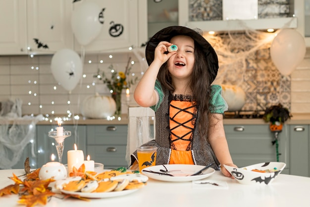 Вид спереди милой маленькой девочки в костюме ведьмы Бесплатные Фотографии