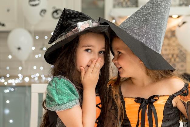 Вид спереди милых маленьких девочек в костюме ведьмы Бесплатные Фотографии