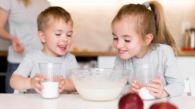 家で料理しているかわいい兄弟の正面図 無料写真