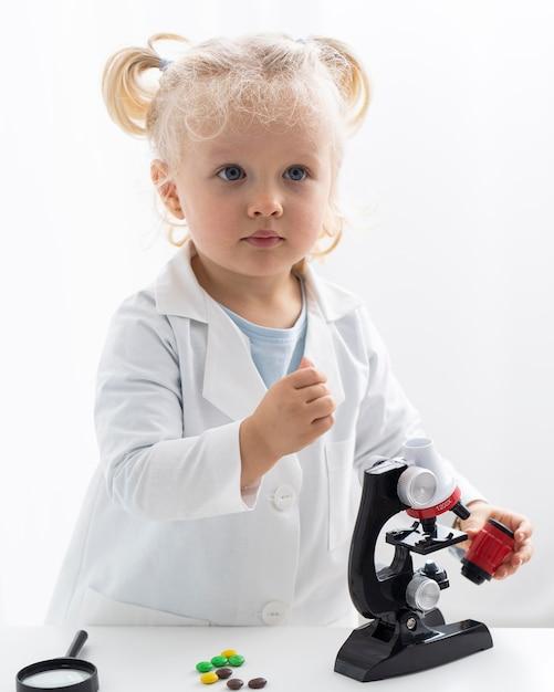 실험실 코트와 현미경으로 귀여운 유아의 전면보기 무료 사진
