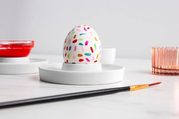 Вид спереди украшенного пасхального яйца на тарелке с краской и кистью Бесплатные Фотографии