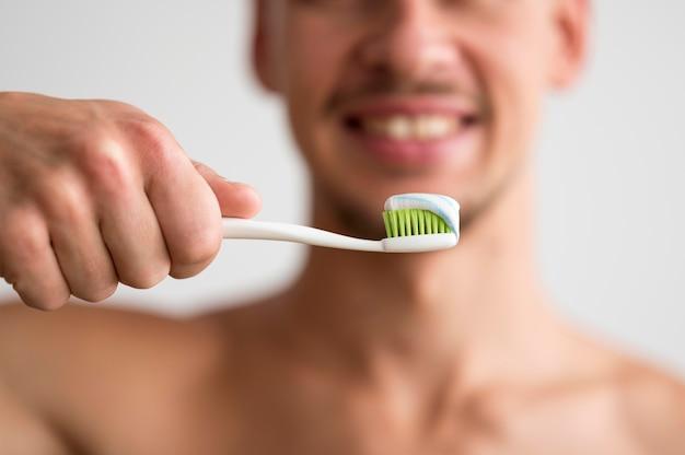 その上に歯磨き粉と歯ブラシを保持している焦点がぼけた男の正面図 無料写真
