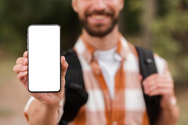 Вид спереди расфокусированного человека с рюкзаком, держащего смартфон Бесплатные Фотографии