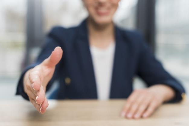 Вид спереди расфокусированным женщина, предлагая дрожание рук после приема на работу Premium Фотографии