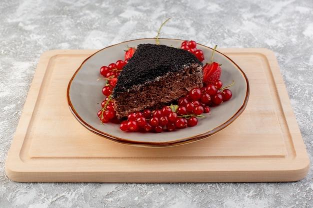 Вид спереди вкусный шоколадный торт нарезанный с шоколадным кремом и свежей красной клюквой на деревянный стол Бесплатные Фотографии