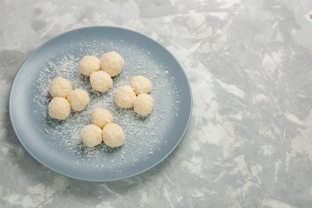 白い壁の青いプレート内のおいしいココナッツキャンディーの正面図 無料写真