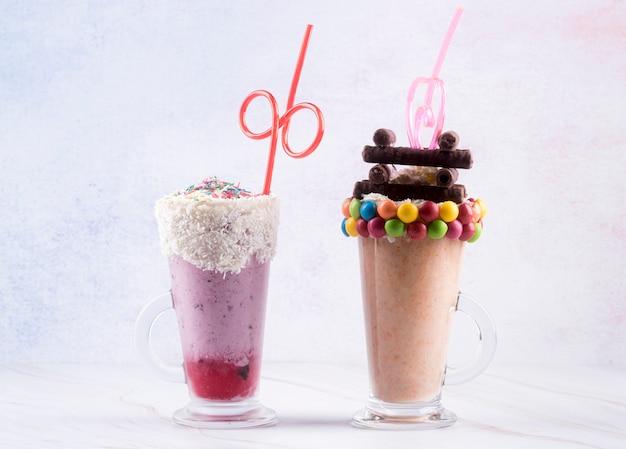 Вид спереди на десертные бокалы с соломкой и разноцветными конфетами Бесплатные Фотографии
