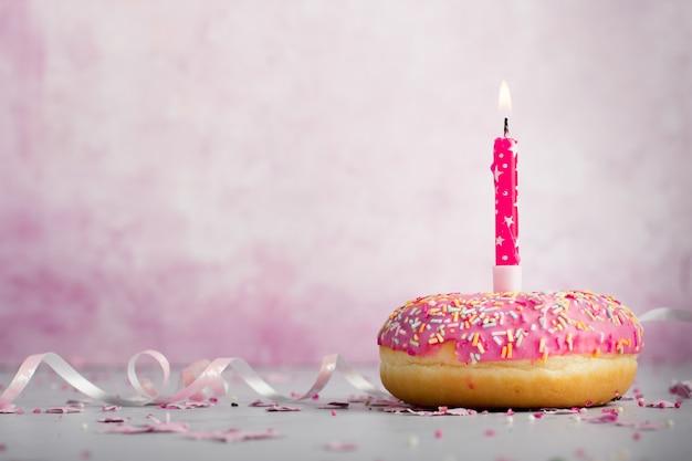 Вид спереди пончик с зажженной свечой и копией пространства Бесплатные Фотографии