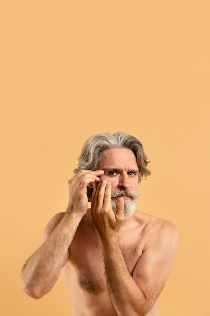 Вид спереди старшего бородатого мужчины, указывая на морщины с копией пространства Бесплатные Фотографии