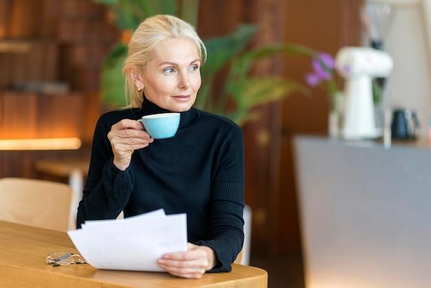 Вид спереди пожилой женщины на работе с кофе и чтением документов Бесплатные Фотографии
