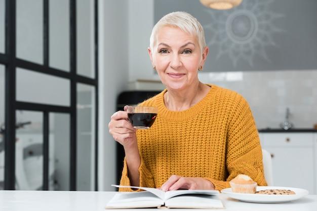 コーヒーカップを保持している高齢者の女性の正面図 無料写真