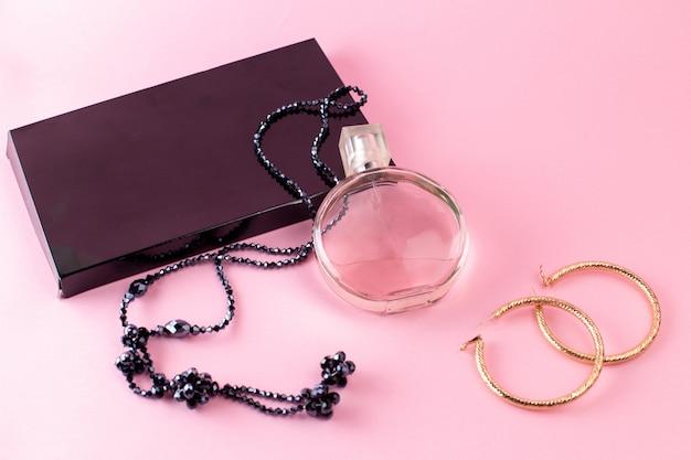 ピンクの表面にネックレスと黒のギフトパッケージを備えたエレガントな香りの正面図 無料写真