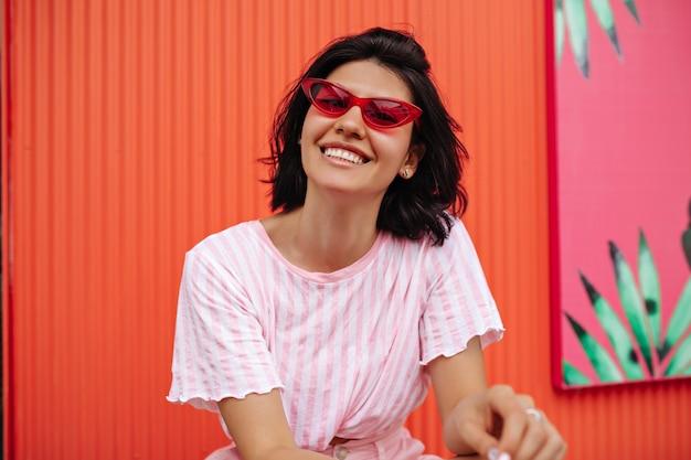 스트라이프 티셔츠에 흥분된 여자의 전면 모습. 핑크 선글라스에 무두 질된 여자 웃음의 야외 샷. 무료 사진