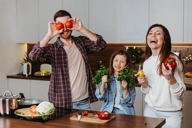 キッチンで食事を準備しながら楽しんでいる家族の正面図 無料写真