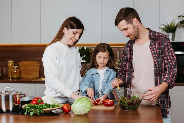 自宅のキッチンで食事を準備している家族の正面図 無料写真