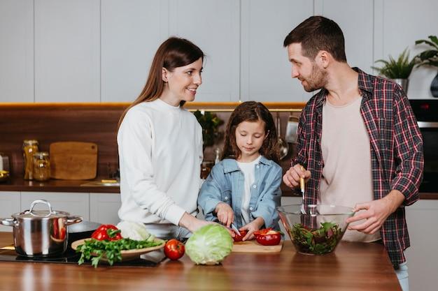 キッチンで食事を準備している家族の正面図 無料写真