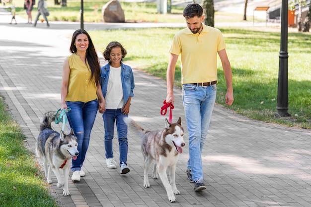 Семья с мальчиком и собакой в парке вместе, вид спереди Бесплатные Фотографии