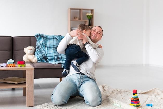 父の子を自宅で保持の正面図 無料写真