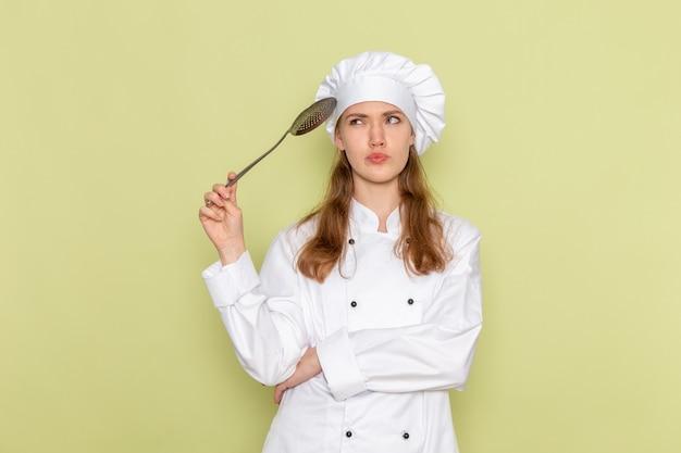 緑の壁に考えて大きな銀のスプーンを保持している白いクックスーツの女性料理人の正面図 無料写真